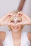 Les mains des femmes formant le coeur tout en tenant la clé de Chambre Photos stock