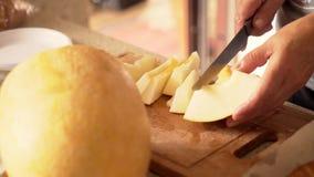 Les mains des femmes ont coupé en morceaux le melon banque de vidéos