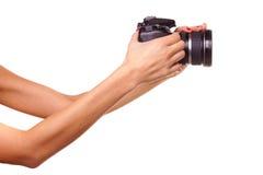 Les mains des femmes retenant l'appareil-photo. Images stock