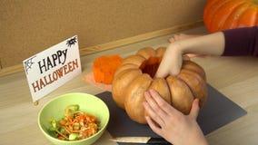 Les mains des femmes retirent des graines d'un potiron pour Halloween banque de vidéos