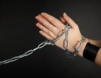 Les mains des femmes shackled un réseau en métal Photographie stock libre de droits