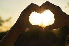 Les mains des femmes sont croisées sous forme de coeur par lequel les rayons de sun font la manière au coucher du soleil Photographie stock libre de droits