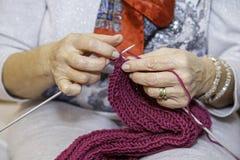 Les mains des femmes tricotant une écharpe Photographie stock libre de droits