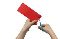 Les mains des hild de ¡ de Ð coupant le papier rouge coloré avec des ciseaux d'isolement Photographie stock