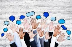 Les mains des hommes d'affaires augmentées avec la bulle de la parole Image stock