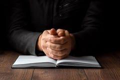Les mains des hommes dans la prière sur un fond noir Le concept de la foi, prière, pleurant, rémission, confession image libre de droits