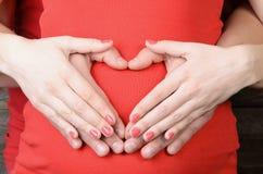 Les mains des hommes et des femmes forment un signe de coeur sur l'estomac Photographie stock libre de droits
