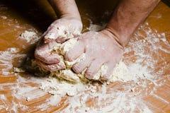 Les mains des hommes malaxent la pâte sur la table en bois Image stock