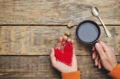 Les mains des hommes tiennent des coeurs de jouet et une tasse de café pour Valentine Photos stock