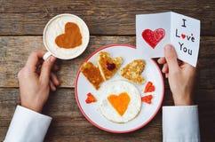 Les mains des hommes tiennent la tasse de café et une carte de voeux pour Valentine Images libres de droits