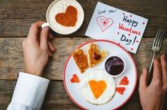 Les mains des hommes tiennent la tasse du café et d'un petit déjeuner pour le D de Valentine Photographie stock libre de droits