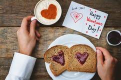Les mains des hommes tiennent la tasse du café et d'un petit déjeuner pour le D de Valentine Images libres de droits