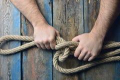 Les mains des hommes tricotent le noeud de corde image libre de droits