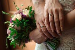 Les mains des jeunes mariés avec des anneaux de mariage, jeune mariée tient un bouquet de mariage dans des mains, le marié l'étre Images stock