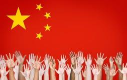 Les mains des personnes augmentées avec le drapeau chinois Photos libres de droits