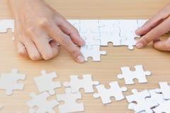 Les mains des personnes diverses assemblant le puzzle denteux, équipe ont mis le morceau image libre de droits