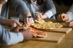 Les mains des personnes diverses prenant la pizza découpe diner en tranches dans la pizzeria Photos stock