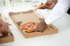 Les mains des personnes diverses prenant des tranches de pizza, se ferment vers le haut de la vue Image stock