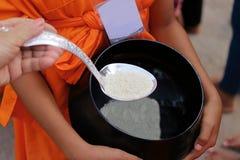 Les mains des personnes thaïlandaises ont mis la nourriture offrant dans la cuvette d'aumône du ` s de moine bouddhiste dans le j images libres de droits