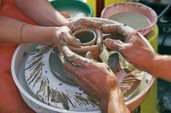 Les mains des potiers guidant les mains du femme Images stock