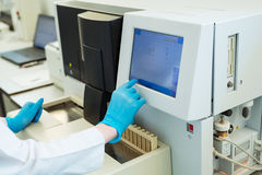 Les mains des tubes témoin de chargement d'assistant de laboratoire pour la coagulation examinent l'analyse et les données inputi Photographie stock