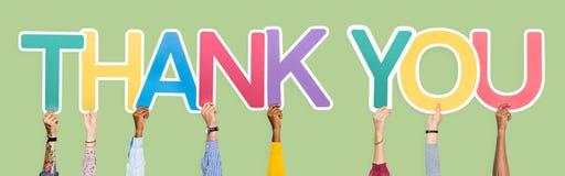 Les mains diverses tenant les mots vous remercient image libre de droits