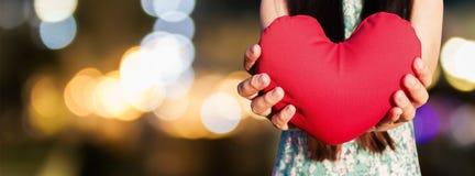 Les mains doucement soulèvent et tiennent le coeur rouge sur le backg de nuit de lumière de bokeh Image libre de droits