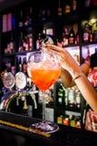 Les mains du barman arrosant l'alcool dans le verre de cocktail rempli de la glace photographie stock libre de droits