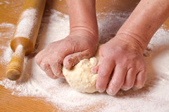 Les mains du boulanger malaxent une pâte de partie Photos stock