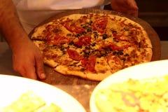 Les mains du boulanger masculin tiennent la pizza de finition image libre de droits