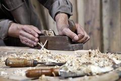 Les mains du charpentier surfacent sur l'établi en menuiserie photos stock
