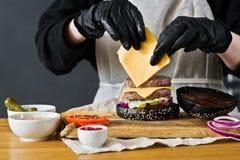 Les mains du chef font cuire les ingrédients d'hamburger Le concept de faire cuire le cheeseburger noir Recette faite maison d'ha photo libre de droits