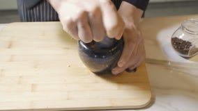 Les mains du chef utilisant un mortier et un pilon en pierre pour rectifier avec confiance une sélection des herbes et des épices clips vidéos