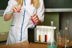 Les mains du chimiste m?lange le fluide des tubes ? essai photos libres de droits