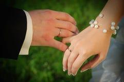 Les mains du couple avec des boucles de mariage Image stock