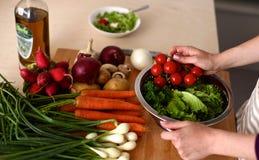 Les mains du cuisinier préparant la salade végétale - plan rapproché Photos stock