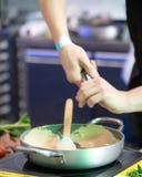 Les mains du cuisinier versent l'assaisonnement dans la poêle Images libres de droits