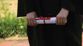 Les mains du diplôme se tenant licencié délivrent un certificat attaché avec le ruban rouge, obtention du diplôme clips vidéos