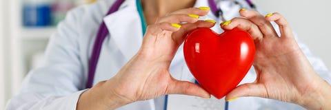 Les mains du docteur féminin de médecine tenant le coeur rouge de jouet image stock