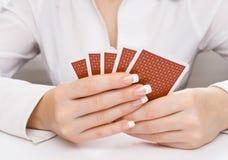 Les mains du femme retenant des cartes de jeu Images libres de droits