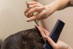 Les mains du jeune coiffeur faisant la coupe de cheveux à l'homme attirant dans le raseur-coiffeur photo stock