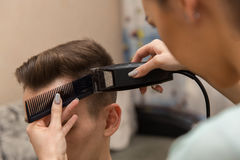 Les mains du jeune coiffeur faisant la coupe de cheveux à l'homme attirant dans le raseur-coiffeur images stock