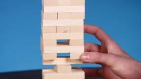 Les mains du jeune homme joue le jenga sur le fond bleu, plan rapproché Un homme construit une tour des blocs tout en jouant le j clips vidéos