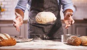 Les mains du mâle du ` s de boulanger malaxent la pâte image stock
