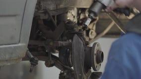 Les mains du maître automatique serrent les vis utilisant la fin d'outil spécial  Homme habile dans l'automobile de réparation un banque de vidéos