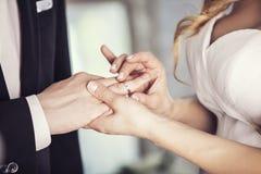 Les mains du marié et de la jeune mariée porte un anneau sur le doigt dessus Images libres de droits