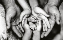 Les mains du père, mère, fille gardent le petit bébé de pieds Famille heureuse amicale images stock