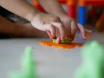 Les mains du petit bébé appliquant la presse en plastique de la pâte sur le playdough photos stock