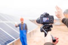 Les mains du photographe montrent un geste, photographiant un travailleur de batterie solaire sur l'appareil-photo outdoors image libre de droits