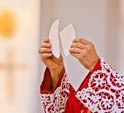 Les mains du prêtre élèvent le corps du Christ images libres de droits